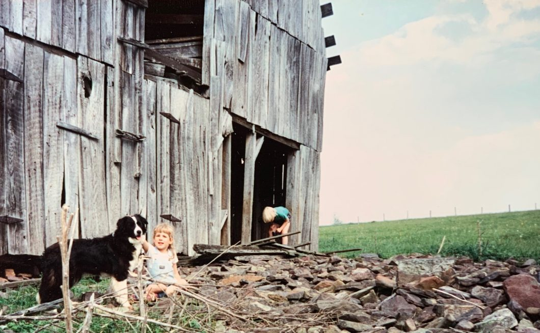 two blond children and border collie playing in front of abandoned barn