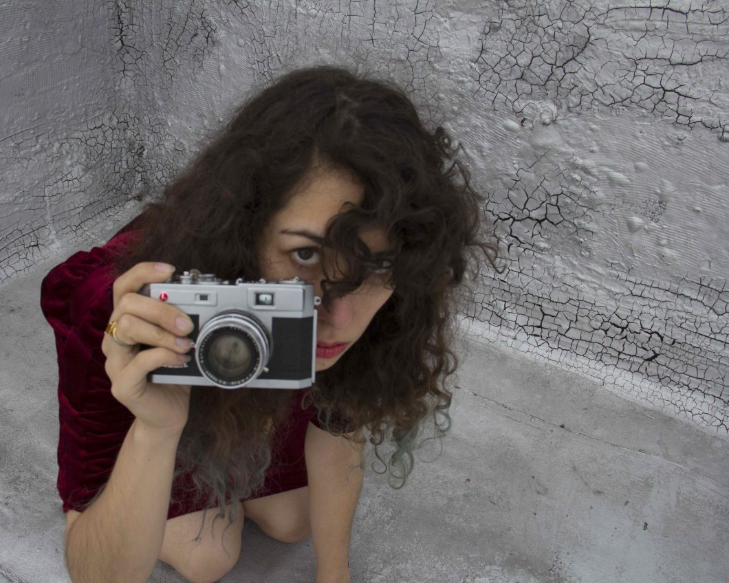image of kneeling girl in a red dress looking at viewer and holding a camera. dark curls of hair obscure part of her face