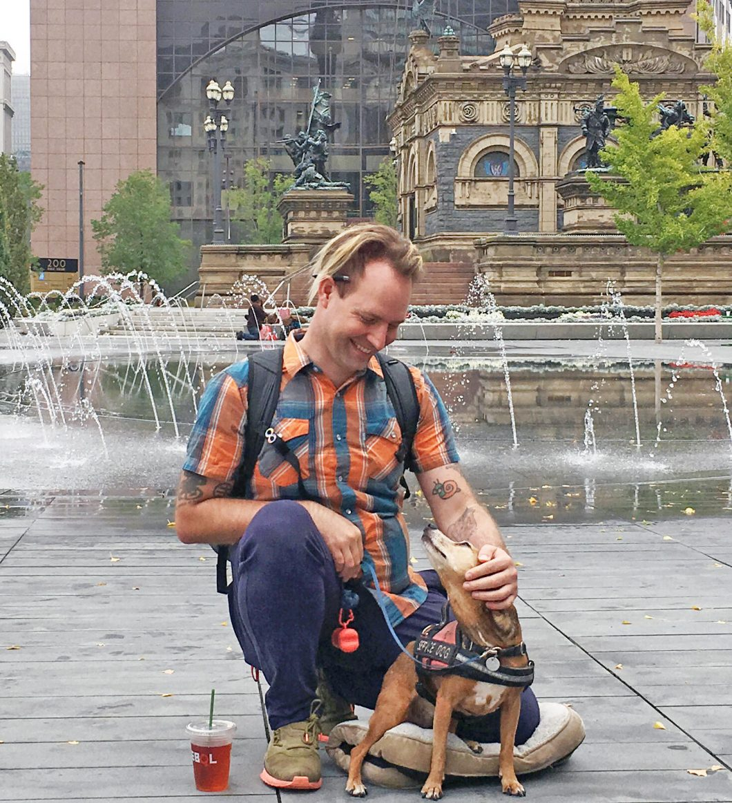 image of kneeling white-skinned man with small service dog in front of a fountain