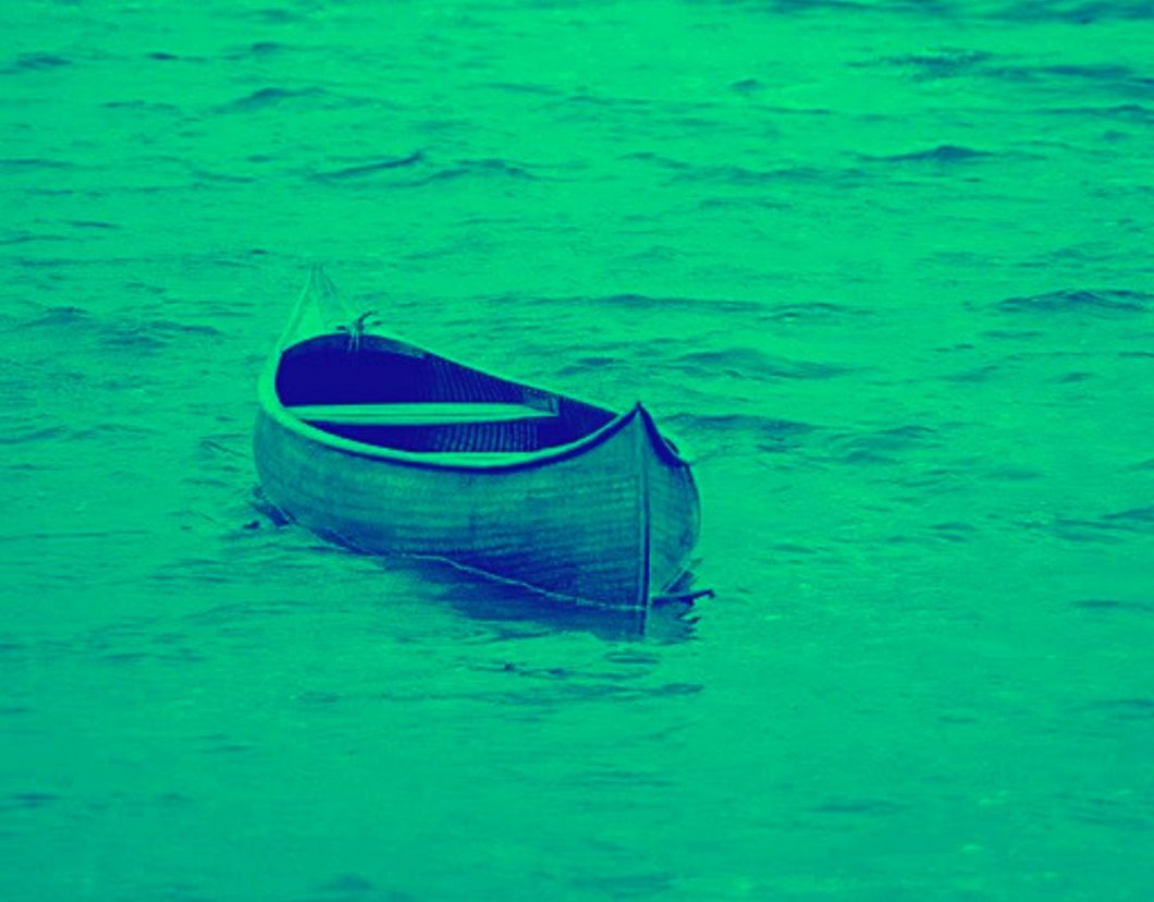 green-filtered image of empty canoe floating on water
