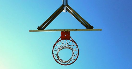 image of basketball hoop from below, silhouetted against a blue sky