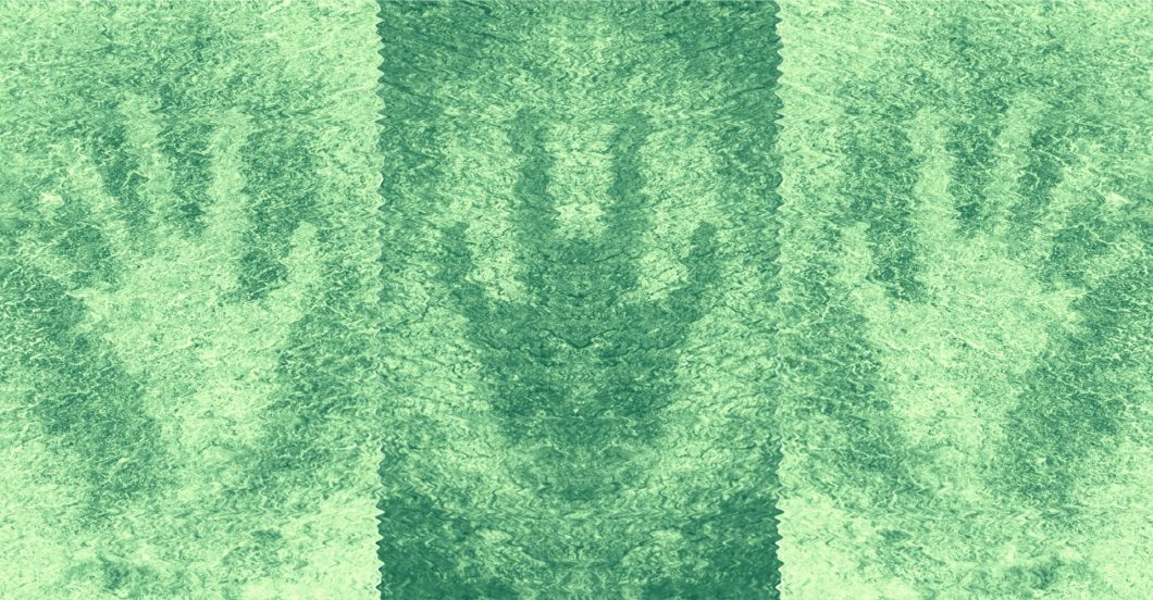Ancient handprints made on rock; mirrored, distorted, and tinted green.